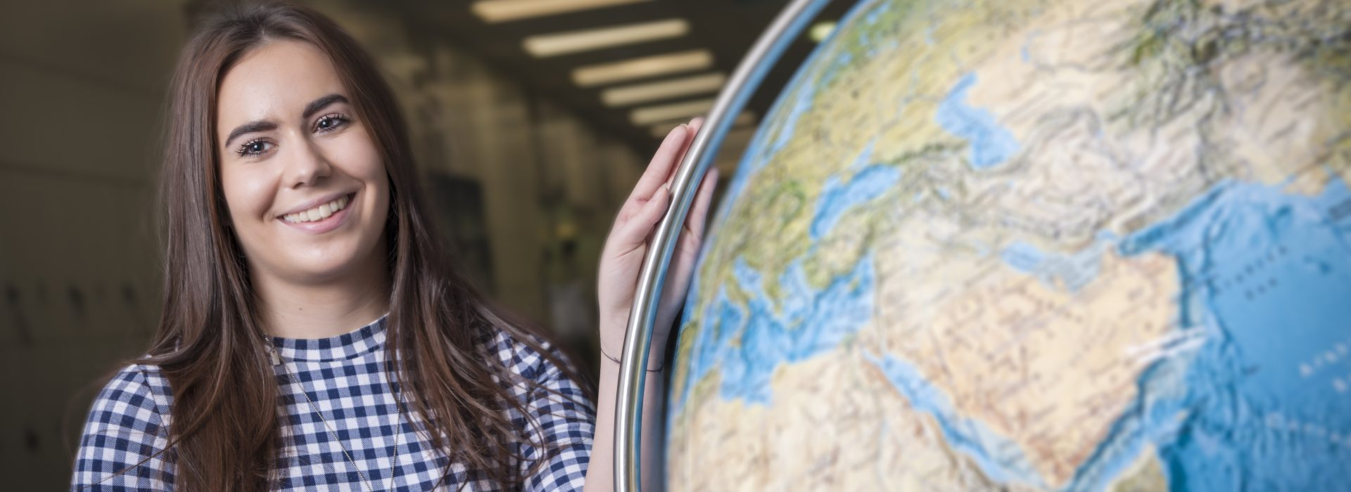 University of Liverpool Geography Course student next to a globe