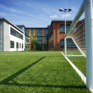 Astroturf pitch showing goal posts with buildings in background at Carmel College, St Helens