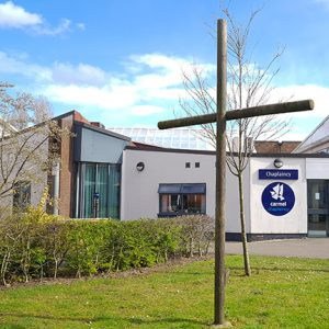 Chaplaincy building, gardens and a wooden cross at Carmel College St Helens