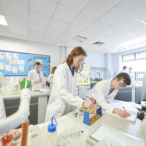 Chemistry students with lab coats on working in a science lab at Carmel College, St Helens