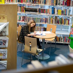 Student sat working at a table inside the library at Carmel College, St Helens