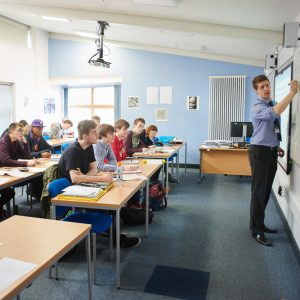 Students sat at desks in a Maths classroom with teacher at the white board at Carmel College St Helens