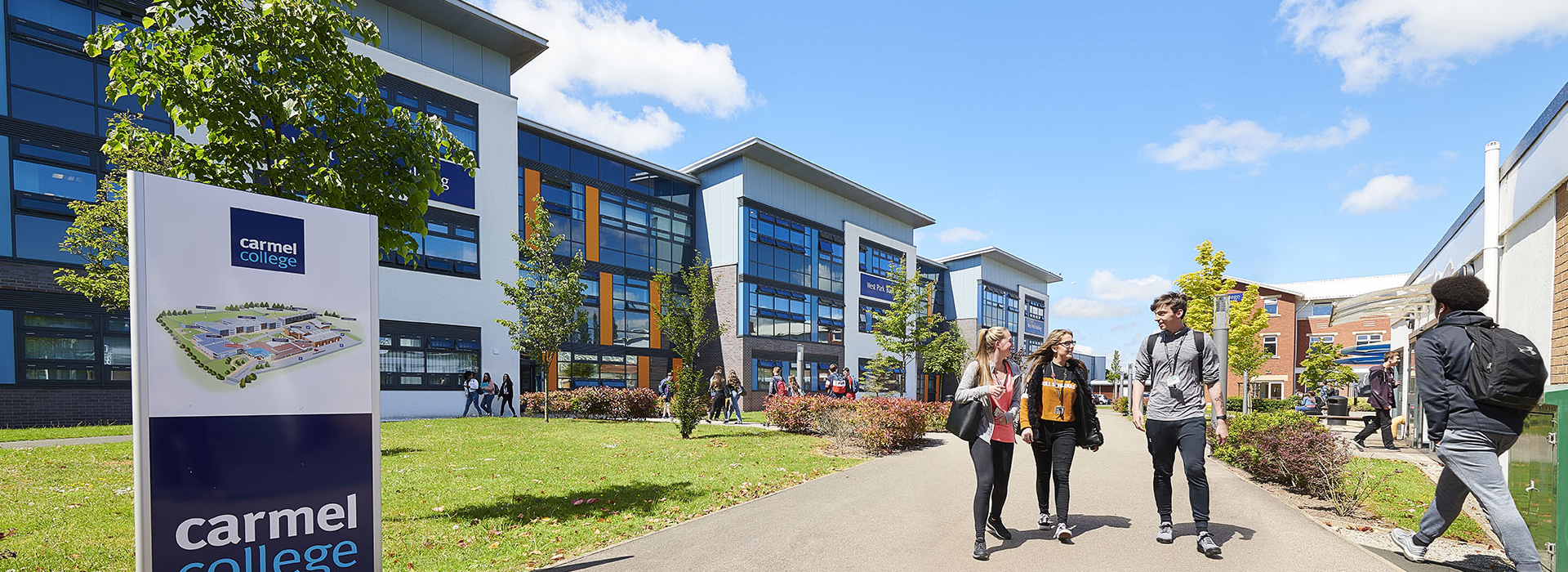a photo of 3 students walking through Carmel College Campus on a sunny day.